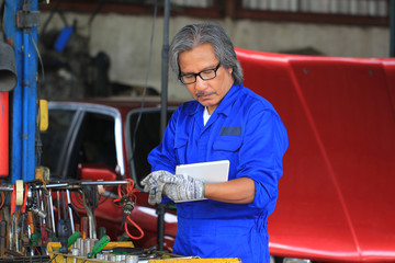 Car mechanic holding digital tablet in auto repair service