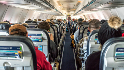 Passengers seated inside of an airplane.