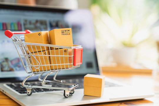 Online shopping and delivery concept, product package boxes in cart and laptop computer on table with copy space.