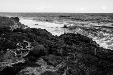Black and white photo strong wave of white sea beats on the rocks