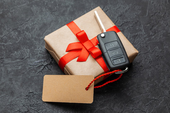 Gift box with car keys with remote control alarm system with red ribbon bow and label.