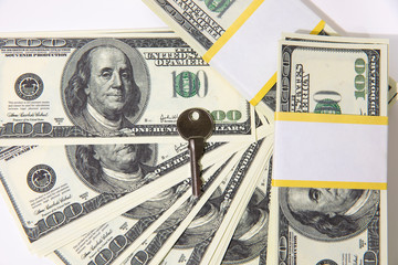 Bundles of hundred dollar banknotes on a white background. House keys. The keys to the apartment on the dollars.