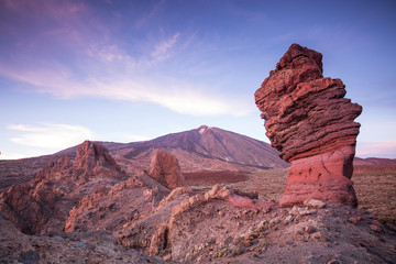 View of the Teide volcano in Canary Islands behind a arid and rocky landscape during a sunny day