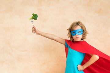 Superhero child eating superfood
