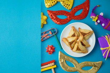 Jewish holiday Purim background with carnival mask, noisemaker and hamantaschen cookies.