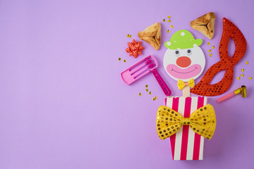 Jewish holiday Purim background with carnival mask, paper clown and hamantaschen cookies.