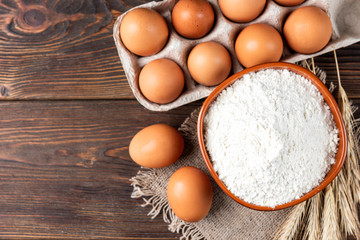 Flour and eggs on dark wooden table. Baking background.