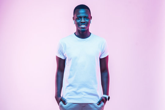 Attractive young african man posing in blank white cotton t-shirt, standing isolated on pink background