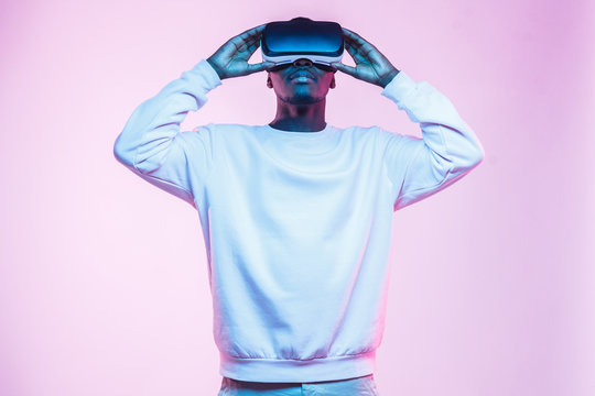 Half-size portrait of African man wearing casual clothes and entertaining in virtual reality, isolated on pink background