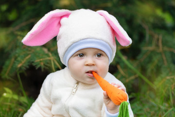 Baby in bunny costume nibbling toy carrot.