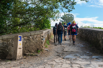 FURELOS, SPAIN - JULY 31, 2016: Some young pilgrims with backpacks cross a medieval bridge, making the Camino de Santiago. Fotomurales
