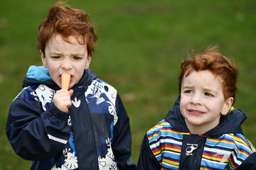 Twins Oisin and Ollie Kiernan, aged 4, eat ice cream while posing for a photograph during 'Kiss a Ginger Day' on the 10-year anniversary of this anti-bullying day, in Dublin