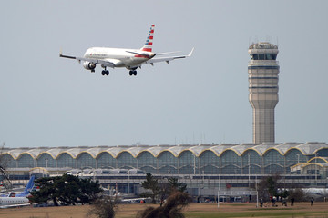 An American Airlines airplane flies past the tower at Reagan National Airport in Washington