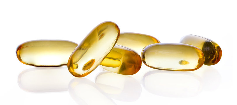 Close up of food supplement oil filled capsules suitable for: fish oil; omega 3; omega 6; omega 9; evening primrose; borage oil; flax seeds oil; vitamin A; vitamin D; vitamin D3; vitamin E