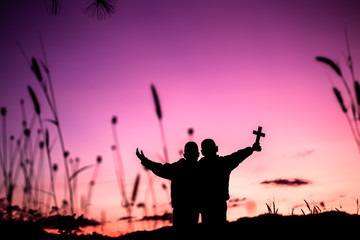 Two children holding cross and worship god with light sunset background,christian concept.