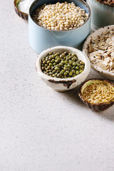 Variety of raw uncooked grains superfood cereal chia seeds, linen, sesame, mung bean, walnuts, tapioca, wheat, buckwheat, oatmeal, coconut, rice in ceramic bowls over grey background. Copy space