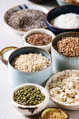Variety of raw uncooked grains superfood cereal chia seeds, linen, sesame, mung bean, walnuts, tapioca, wheat, buckwheat, oatmeal, coconut, rice in ceramic bowls over grey spotted background. Close up