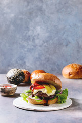 Variety of homemade classic and mini burgers in wheat and black buns with beef and veal cutlets, melted cheese and vegetables on white ceramic board over grey blue table.