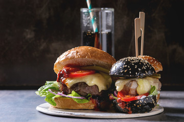 Variety of homemade classic and mini burgers in wheat and black buns with beef and veal cutlets, melted cheese and vegetables on white ceramic board over dark table. With glass of cola.
