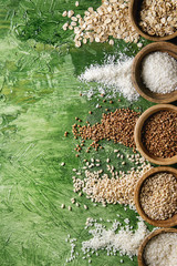 Variety of raw uncooked grains superfood cereal linen seeds, sesame, mung bean, wheat, buckwheat, oatmeal, coconut, rice in wooden bowls over green texture background. Flat lay, space