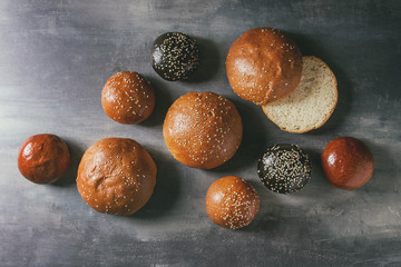 Variety of homemade traditional and black cuttlefish ink different size burger buns with sesame seeds whole and sliced over blue texture background. Flat lay, space