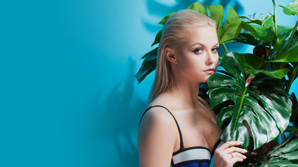 Young woman in blue bikini on blue background.