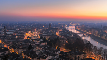Panoramic view of the city of Verona with night city illumination and the Adige river with bridges covered with the evening mist colored by the setting sun. Sunset in Verona. Winter time. Italy.