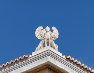 Athens Greece, double sphinx statue on blue sky background