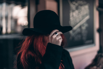 girl with red hair hold a black hat