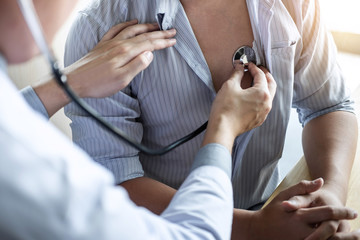 Doctor using a stethoscope checking patient with examining, presenting results symptom and...