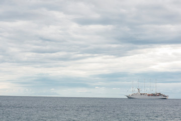 Cruising ship on empty sea with beautiful dramatic clouds