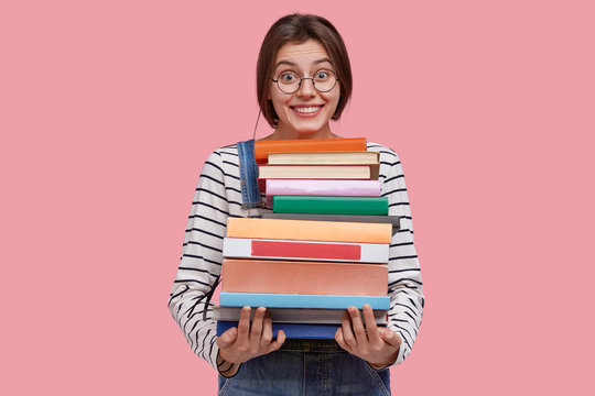 Delighted young woman carries pile of textbooks, smiles broadly, learns useful information from encyclopedia, has dark hair, dressed in casual outfit, poses aginst pink background. Education concept