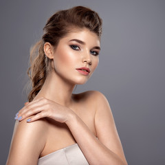 Beautiful face of young caucasian woman with perfect health skin - over grey background. Skin care concept. Female Model touches body.