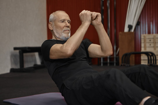 Cropped shot of handsome unshaven seventy year old male with athletic healthy body exercising on mat, holding hands in front of him, doing sit ups or crunches to strengthen abdominal muscles