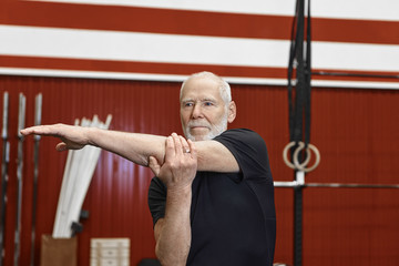 Handsome blue eyed retired male with wrinkled face, gray beard and muscular body, warming up before workout, stretching arms in stylish modern gym. Age, people, lifestyle, activity and exercise