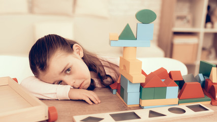 Sad Little Girl Playing with Kids Cubes at Home.