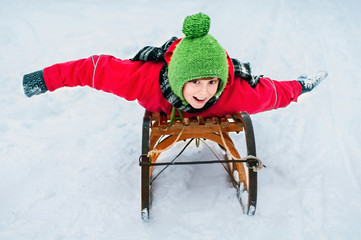 Happy child riding down a hill on an old wooden sled. Winter out