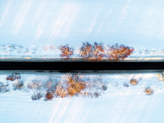Aerial view of a car on winter road in the forest. Winter landscape countryside. Aerial photography of snowy forest with a car on the road. Captured from above. Aerial photo. Car in motion