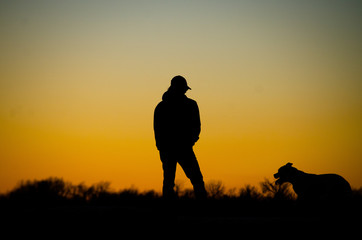 silhouette of man in sunset with dog