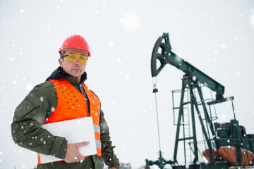 Oil and gas Drill field ,pump jack with snow storm and worker with laptop  looking at camera