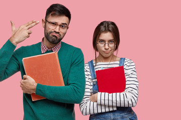 Frustrated male student shoots in temple, feels tired of long learning, holds book, stands near sad girlfriend in overalls, being overworked, isolated over pink background. Friendship concept