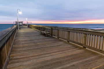Sunrise from the Sandbridge Fishing Pier on Little Island Park in Virginia Beach.  The wood of the pier is lit by early morning sun rising in the clouds, creating pink and purple light.
