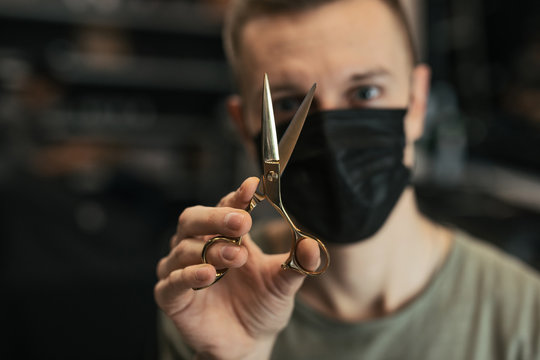 Hairdresser wear mask and hold scissors near his face. - Image