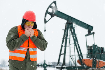 Oil Drill field , pump jack in the background .Oil and gas industry worker in safety clothing get it frozen in front , blowing hot air in his clasped hands