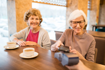 Cheerful modern senior ladies paying for tea with smartphone: smiling gray-haired lady sitting at table and putting gadget to payment terminal