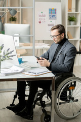 Serious office worker sitting in wheelchair at the table and reading a message in mobile phone at office