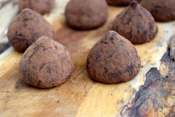 Ttruffles are on a wooden surface. Truffles are the candies made of chocolate. Candies have round shape