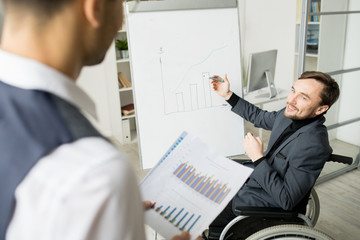 Young disabled businessman sitting in wheelchair and presenting his financial report on whiteboard to his partner