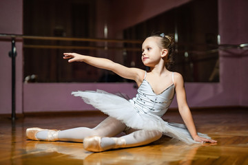 Adorable small ballerina in white tutu sitting on wooden floor and pointing with her right hand at ballet class. Little dancer doing exercises in studio