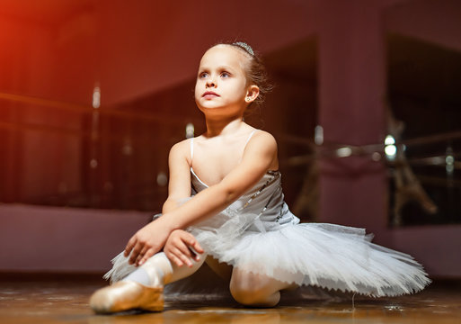 Little ballerina in white tutu sitting on floor and resting in dance studio. Pretty small girl in ballet suit sits on the wooden floor and dreaming